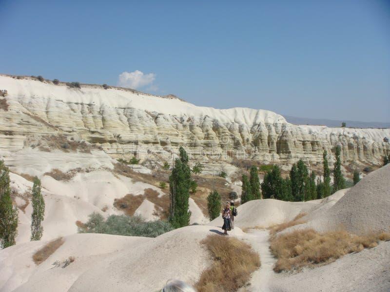 Περπατώντας άνθρωποι στο χαρακτηριστικό πανόραμα των άσπρων βράχων του φυσικού πάρκου Goreme σε Capadoccia στην Τουρκία στοκ εικόνες με δικαίωμα ελεύθερης χρήσης
