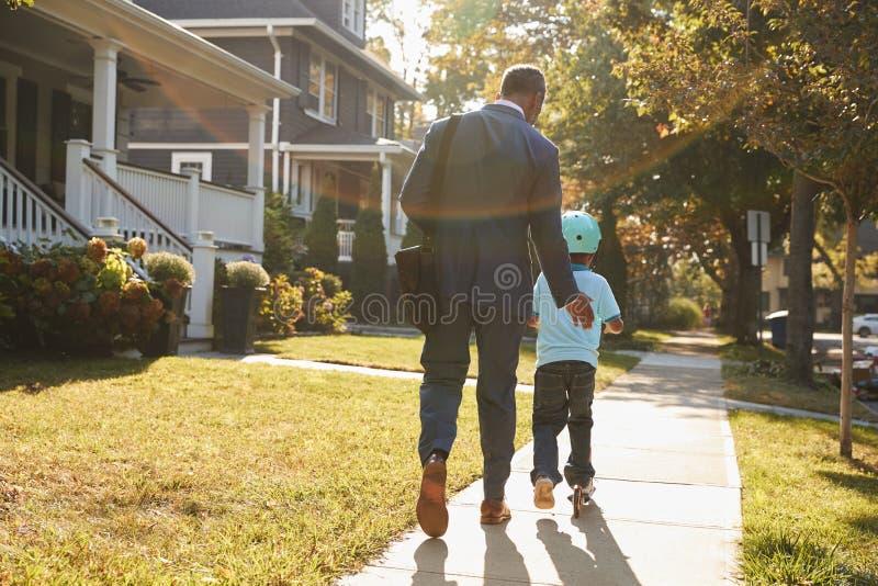 Περπατώντας γιος πατέρων επιχειρηματιών στο μηχανικό δίκυκλο στο σχολείο στοκ φωτογραφία με δικαίωμα ελεύθερης χρήσης