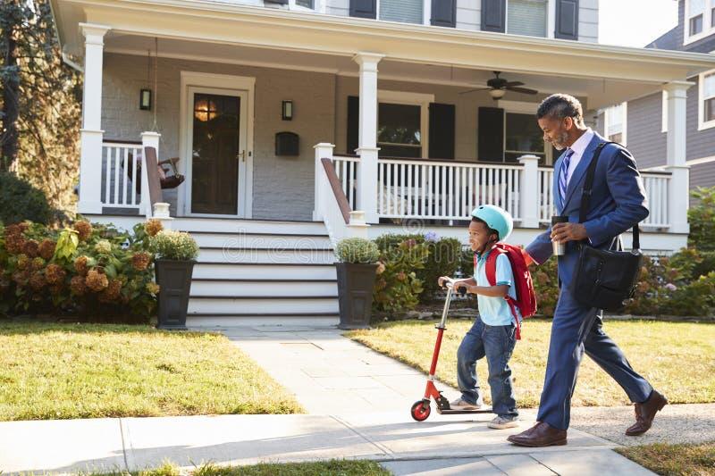 Περπατώντας γιος πατέρων επιχειρηματιών στο μηχανικό δίκυκλο στο σχολείο στοκ εικόνα