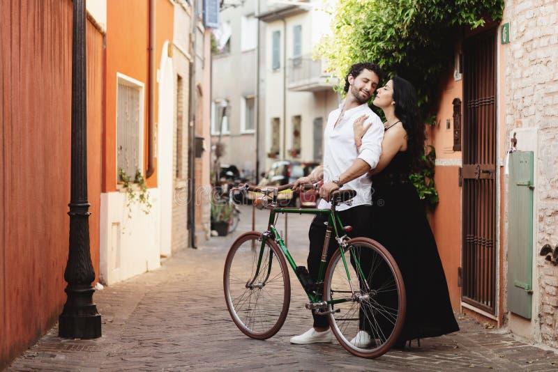 Περπατώντας μερικούς εραστές στις οδούς της παλαιάς πόλης, με ένα ποδήλατο Η γυναίκα αγκαλιάζει ήπια τον άνδρα της στοκ εικόνες
