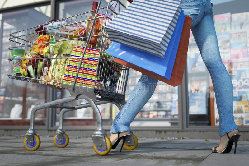 Περπατώντας τσάντα εκμετάλλευσης γυναικών αγορών και καροτσάκι αγορών κοντά επάνω στοκ φωτογραφίες