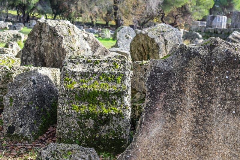 Πεσμένα κομμάτια των κλασσικών στυλοβατών που κοιλαίνουν με το βρύο ηλικίας και ανάπτυξης επί του τόπου της αρχαίας Ολυμπία όπου  στοκ εικόνες με δικαίωμα ελεύθερης χρήσης