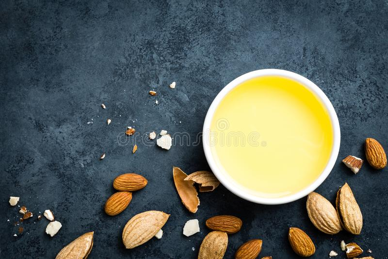 Πετρέλαιο αμυγδάλων στα καρύδια κύπελλων και αμυγδάλων νύξεων στοκ εικόνα με δικαίωμα ελεύθερης χρήσης
