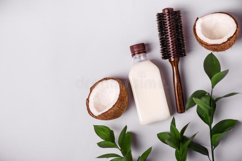 Πετρέλαιο καρύδων και τροπικά φύλλα Έννοια τρίχας care spa στοκ εικόνα