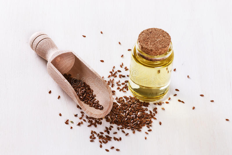 Πετρέλαιο λιναρόσπορου και flaxseed πέρα από το άσπρο υπόβαθρο στοκ φωτογραφία