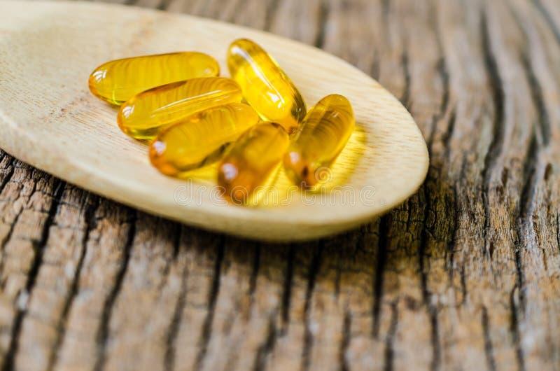 Πετρέλαιο ψαριών στο ξύλινο κουτάλι με την ξύλινη σύσταση στοκ φωτογραφία