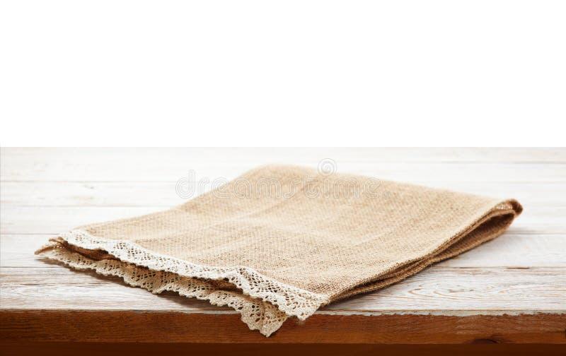 Πετσέτα καμβά με τη δαντέλλα, τραπεζομάντιλο στον ξύλινο πίνακα στο άσπρο υπόβαθρο μπορέστε χρησιμοποιημένος για την επίδειξη ή τ στοκ εικόνα