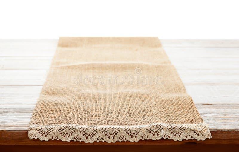 Πετσέτα καμβά με τη δαντέλλα, τραπεζομάντιλο στον ξύλινο πίνακα στο άσπρο υπόβαθρο μπορέστε χρησιμοποιημένος για την επίδειξη ή τ στοκ φωτογραφία με δικαίωμα ελεύθερης χρήσης