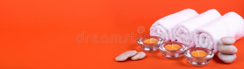 Πετσέτες, κεριά για μια χαλάρωση SPA στο πορτοκαλί υπόβαθρο απαγορευμένα στοκ φωτογραφίες με δικαίωμα ελεύθερης χρήσης