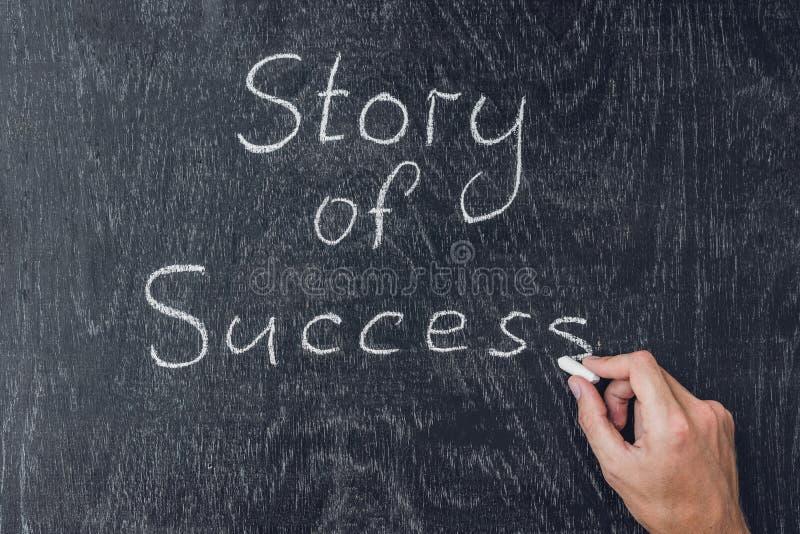 Πετυχημένες ιστορίες που γράφονται στον πίνακα που χρησιμοποιεί την κιμωλία στοκ φωτογραφία