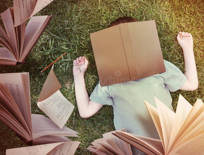 Πετώντας βιβλία γύρω από το αγόρι ύπνου στη χλόη στοκ εικόνες