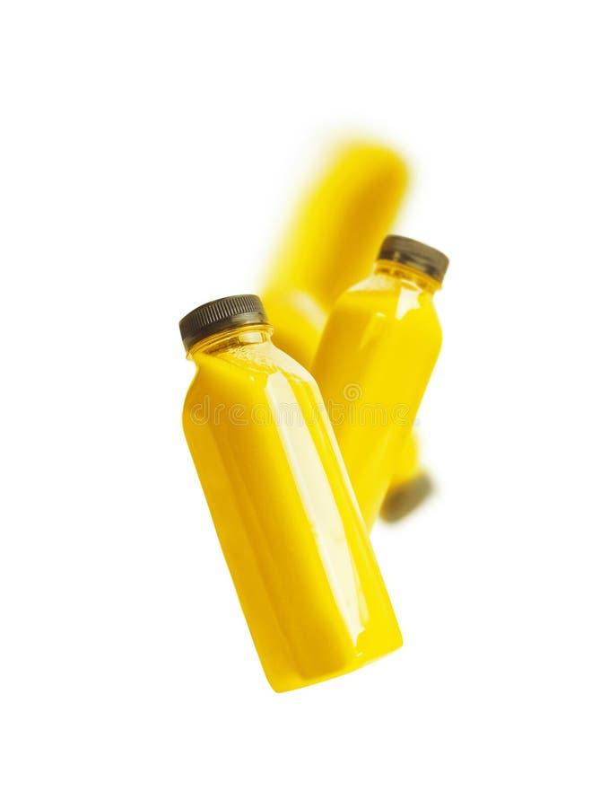 Πετώντας κίτρινο μπουκάλι καταφερτζήδων ή χυμού, που απομονώνεται στο άσπρο υπόβαθρο στοκ φωτογραφία με δικαίωμα ελεύθερης χρήσης
