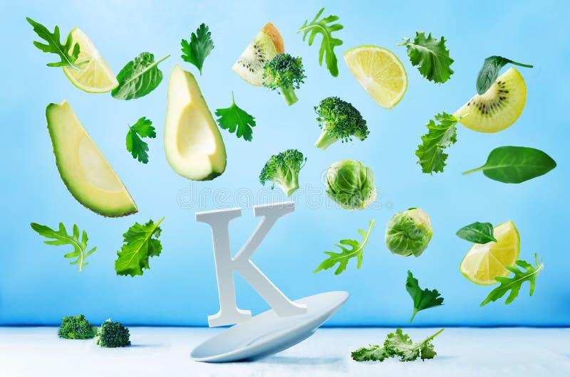 Πετώντας τρόφιμα πλούσια σε βιταμίνη Κ πράσινα λαχανικά στοκ φωτογραφία