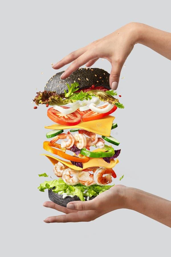 Πετώντας burger με τα φρέσκα συστατικά μεταξύ των χεριών της γυναίκας σε ένα ελαφρύ υπόβαθρο στοκ εικόνες