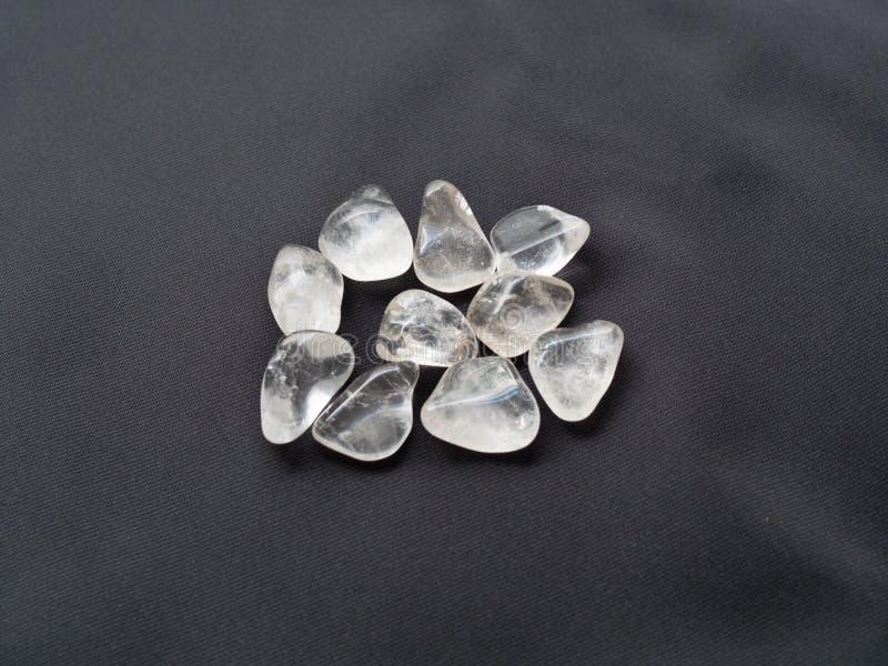 Πεφμένες ρόδινες πέτρες χαλαζία κοντά επάνω στο μαύρο ύφασμα για το κρύσταλλο τ στοκ εικόνες
