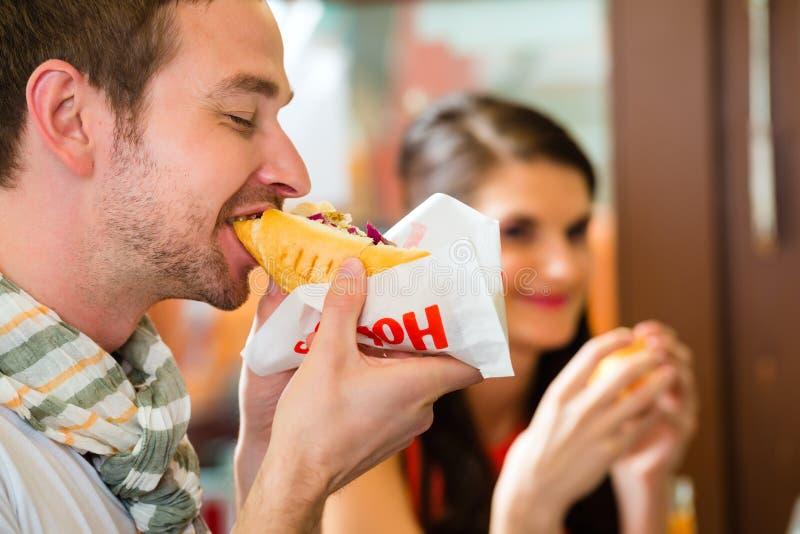 Πελάτες που τρώνε το χοτ ντογκ στο φραγμό πρόχειρων φαγητών γρήγορου φαγητού στοκ εικόνες