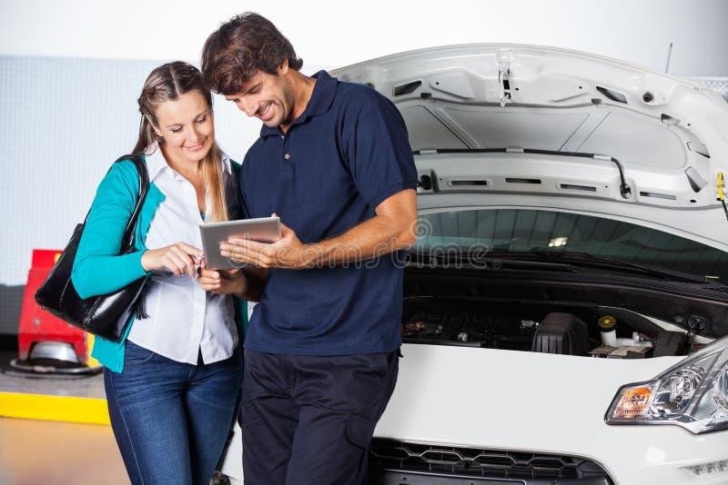 Πελάτης και τεχνικός που χρησιμοποιούν την ψηφιακή ταμπλέτα μέσα στοκ εικόνα
