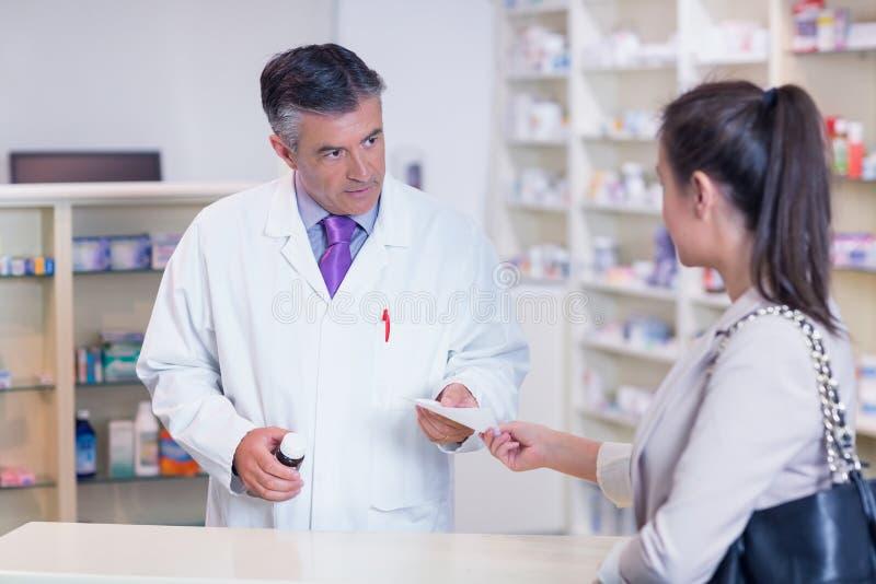 Πελάτης που δίνει μια συνταγή σε έναν φαρμακοποιό στοκ φωτογραφία με δικαίωμα ελεύθερης χρήσης