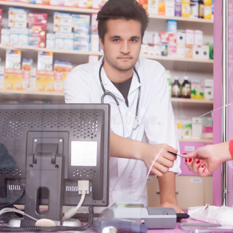 Πελάτης που δίνει την πιστωτική κάρτα στο φαρμακοποιό στο φαρμακείο στοκ εικόνα