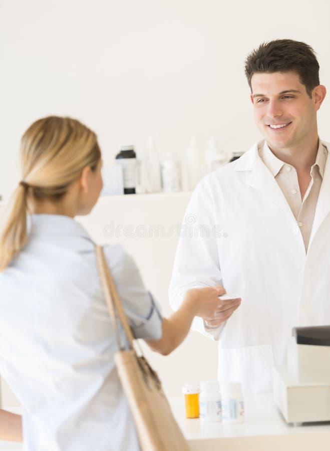 Πελάτης που δίνει το έγγραφο συνταγών στο φαρμακοποιό στο κατάστημα στοκ εικόνες