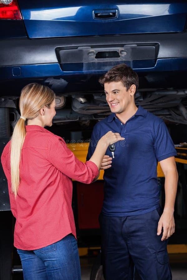 Πελάτης που δίνει το κλειδί αυτοκινήτων στο μηχανικό στοκ εικόνες