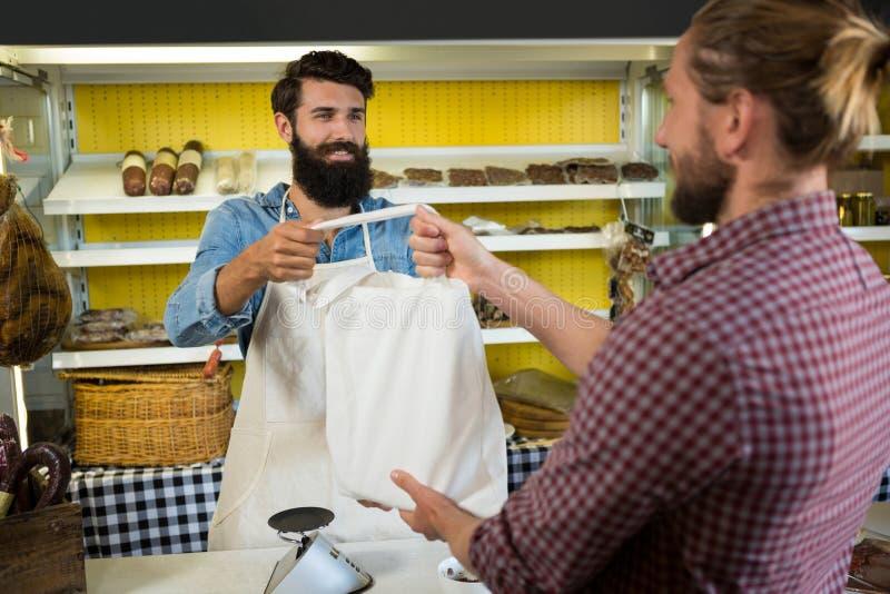 Πελάτης που λαμβάνει το δέμα στο μετρητή κρέατος στοκ εικόνες με δικαίωμα ελεύθερης χρήσης