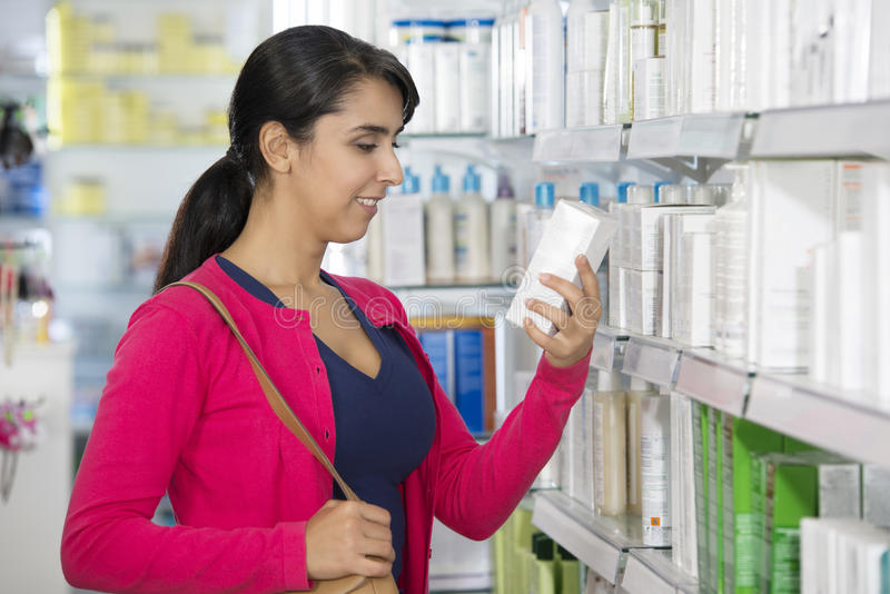 Πελάτης που εξετάζει το προϊόν από τα ράφια στο φαρμακείο στοκ φωτογραφίες με δικαίωμα ελεύθερης χρήσης