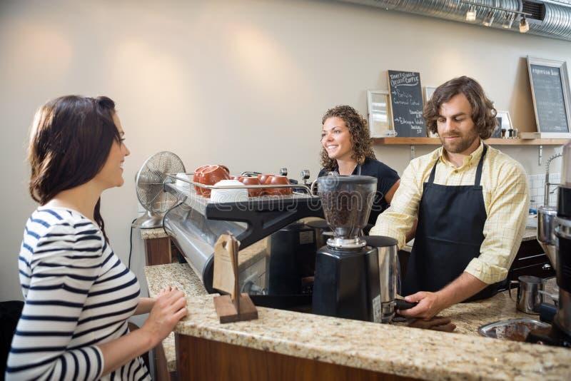 Πελάτης που εξετάζει Baristas που κατασκευάζει τον καφέ μέσα στοκ φωτογραφία