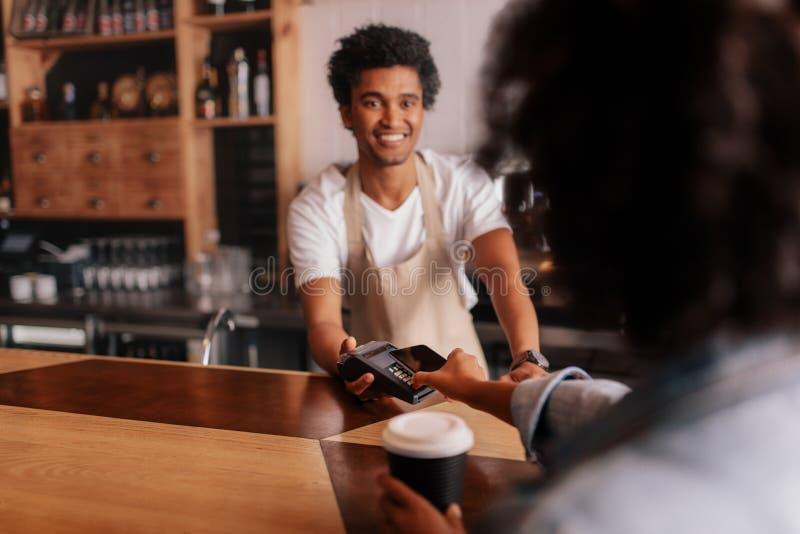 Πελάτης που κάνει την πληρωμή μέσω του κινητού τηλεφώνου στο μετρητή στον καφέ στοκ εικόνες με δικαίωμα ελεύθερης χρήσης