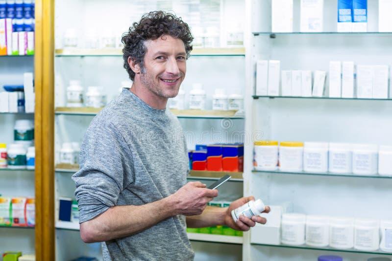 Πελάτης που χρησιμοποιεί το κινητό τηλέφωνο με ένα μπουκάλι του φαρμάκου υπό εξέταση στοκ εικόνες