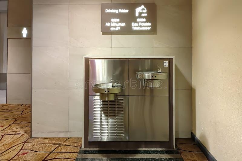 Πηγή κατανάλωσης νερού σε έναν δημόσιο χώρο Σύγχρονη συσκευή του ανοξείδωτου για την κατανάλωση στον αερολιμένα στοκ εικόνα με δικαίωμα ελεύθερης χρήσης