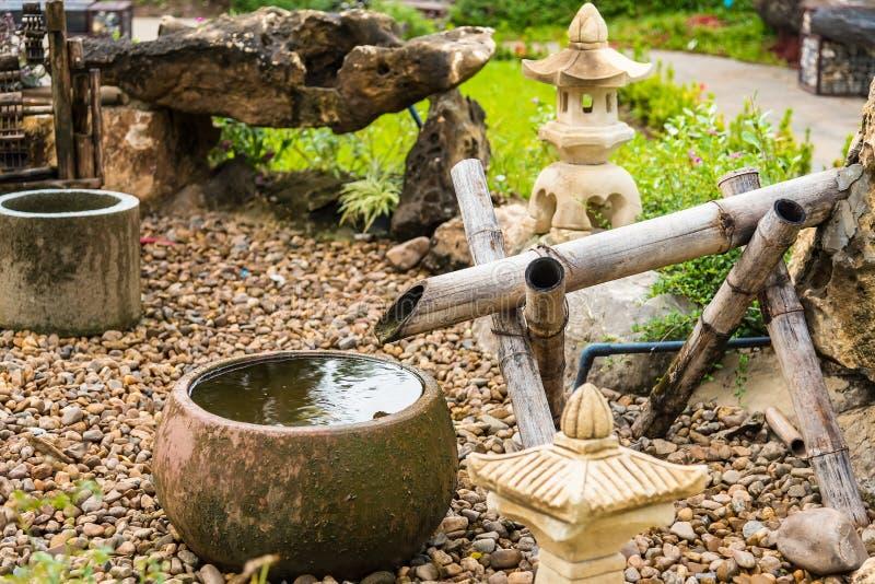 Πηγή νερού με το πέτρινο βύσμα λεκανών και μπαμπού και πέτρινο φανάρι στον κήπο στοκ εικόνα