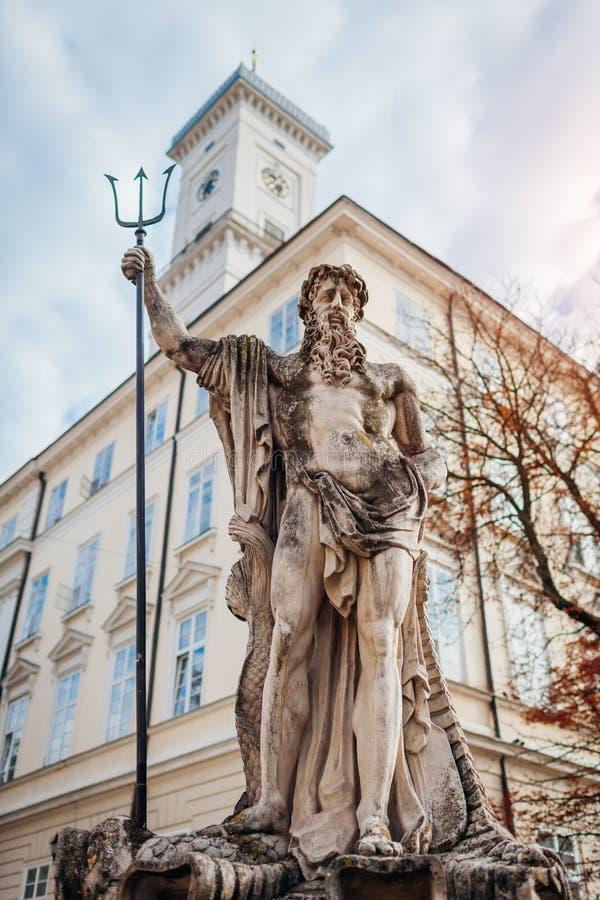 Πηγή Ποσειδώνα στο τετράγωνο αγοράς σε Lviv στο υπόβαθρο Δημαρχείων Τουρισμός στοκ εικόνα με δικαίωμα ελεύθερης χρήσης