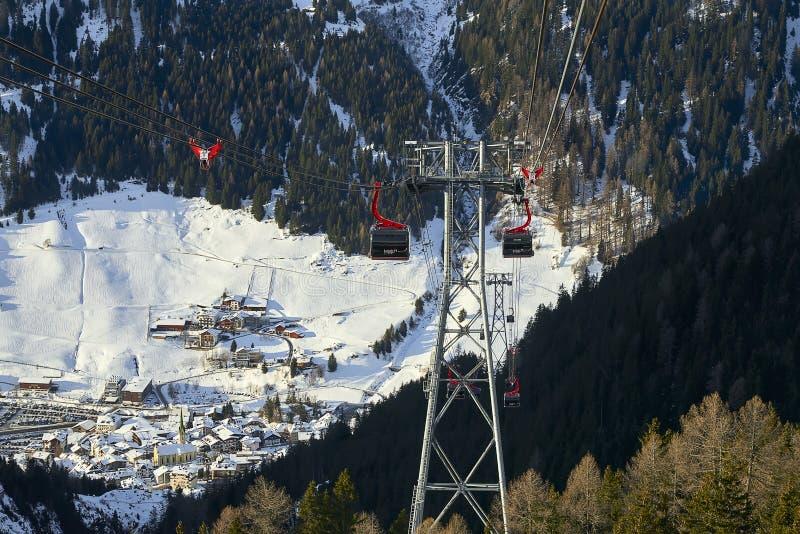 Πηγαίνοντας προς τα κάτω τελεφερίκ γονδολών funifor στη βουνοπλαγιά στην ηλιόλουστη χειμερινή ημέρα, χιονοδρομικό κέντρο στις Άλπ στοκ φωτογραφία
