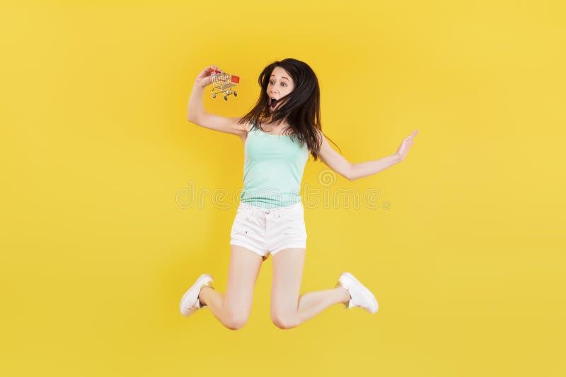 Πηδώντας κορίτσι με το κάρρο αγορών στοκ εικόνες