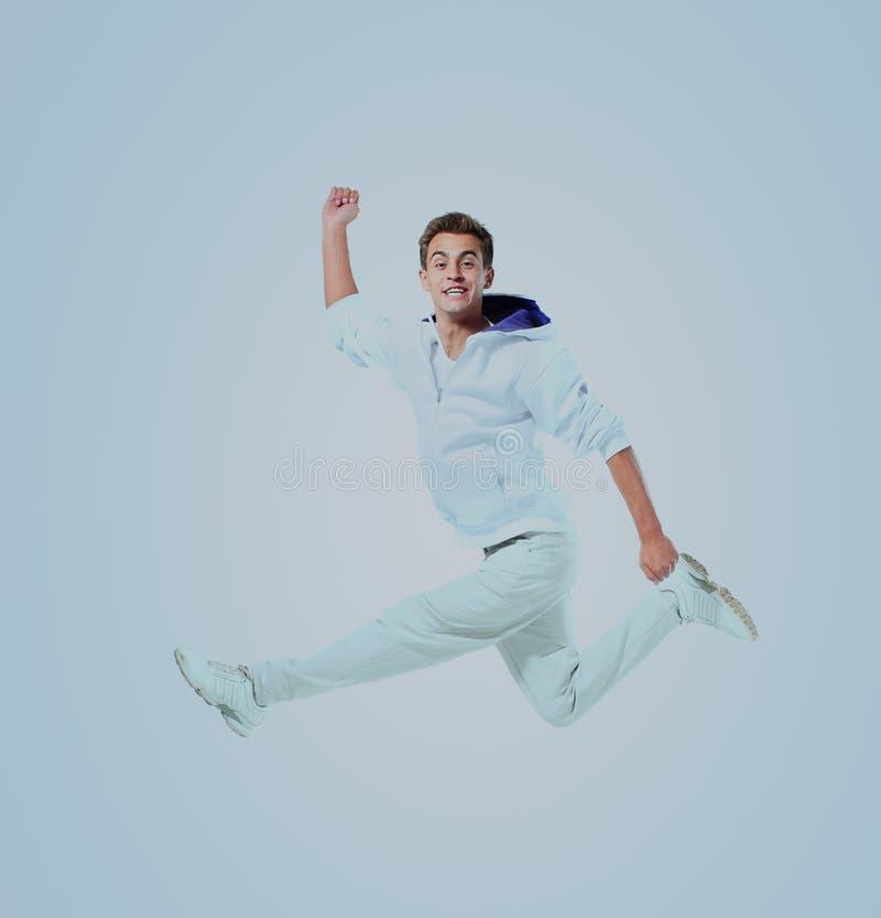 Πηδώντας νεαρός άνδρας Απομονωμένος πέρα από την μπλε ανασκόπηση στοκ εικόνες