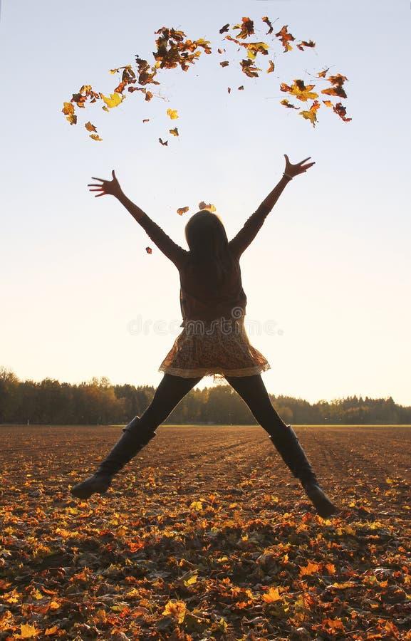 Πηδώντας έφηβη, που ρίχνει τα φύλλα επάνω στον αέρα στοκ φωτογραφία με δικαίωμα ελεύθερης χρήσης