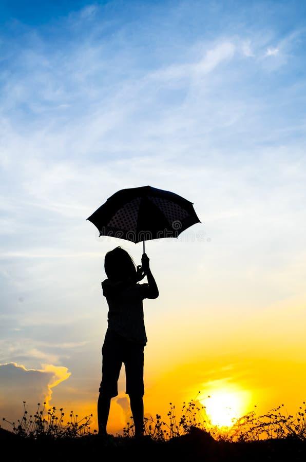 Πηδώντας κορίτσι ομπρελών θαμπάδων κινήσεων με το ηλιοβασίλεμα στοκ φωτογραφία με δικαίωμα ελεύθερης χρήσης