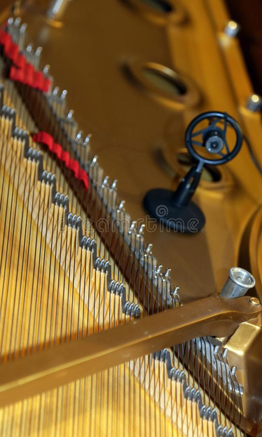 Πιάνο με λίγο σφυρί και τις σειρές και το μικρόφωνο στοκ εικόνα