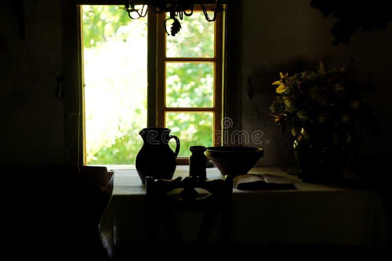 Πιάτα αργίλου, βιβλίο και ανθοδέσμη λουλουδιών στον πίνακα κοντά στο ανοικτό παράθυρο Εκλεκτής ποιότητας αναδρομική ακόμα φωτογρα στοκ φωτογραφία με δικαίωμα ελεύθερης χρήσης
