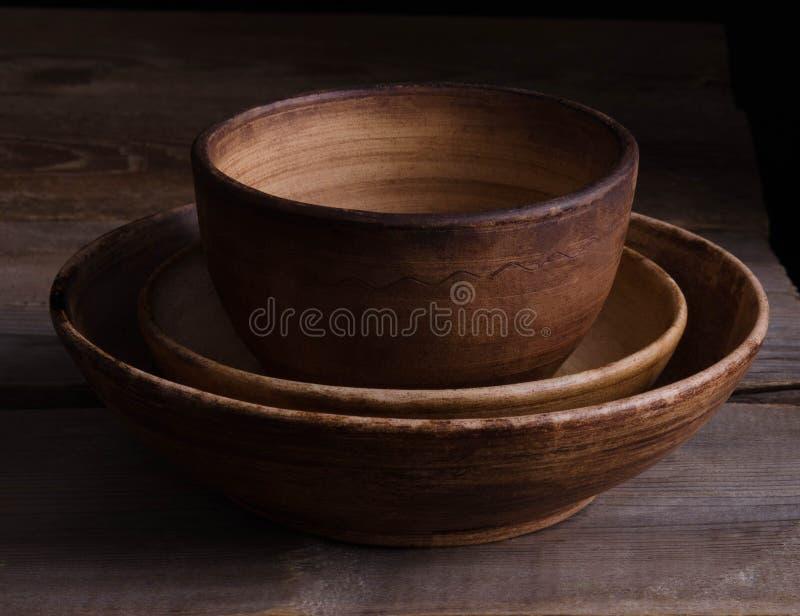 Πιάτα αργίλου στον παλαιό ξύλινο πίνακα στοκ φωτογραφία