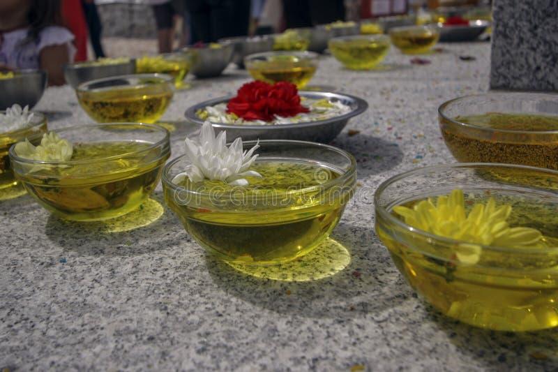 Πιάτα γυαλιού με το κίτρινα ουσιαστικό πετρέλαιο και τα λουλούδια στοκ εικόνες