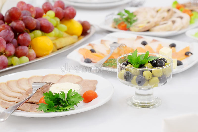 Πιάτα και τρόφιμα στον εξυπηρετούμενο πίνακα στοκ εικόνες