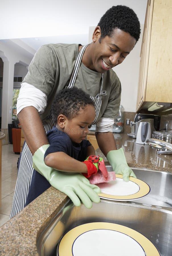 Πιάτα πλύσης ατόμων με το γιο στοκ εικόνες