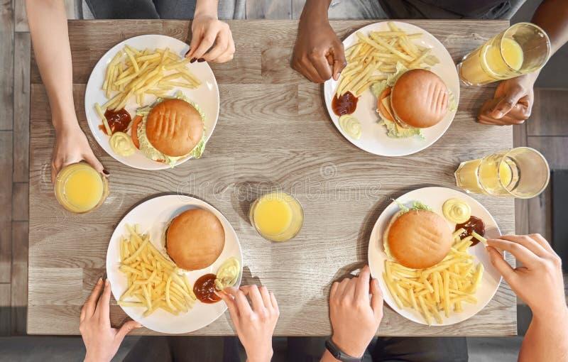 Πιάτα των χάμπουργκερ, τηγανιτές πατάτες, γυαλιά χυμού στον πίνακα στοκ εικόνα