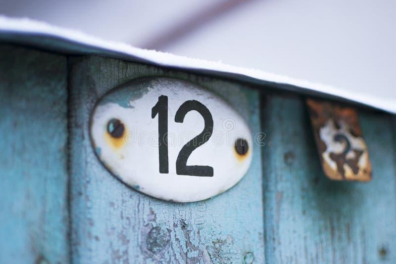 Πιάτο αριθμός δώδεκα στη shabby πόρτα στοκ εικόνα