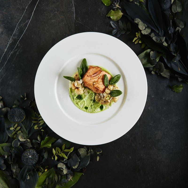 Πιάτο εστιατορίων με τη λωρίδα του σολομού 48 βαθμοί, κρέμα πράσινων μπιζελιών και μμένη τοπ άποψη κουνουπιδιών στοκ φωτογραφία