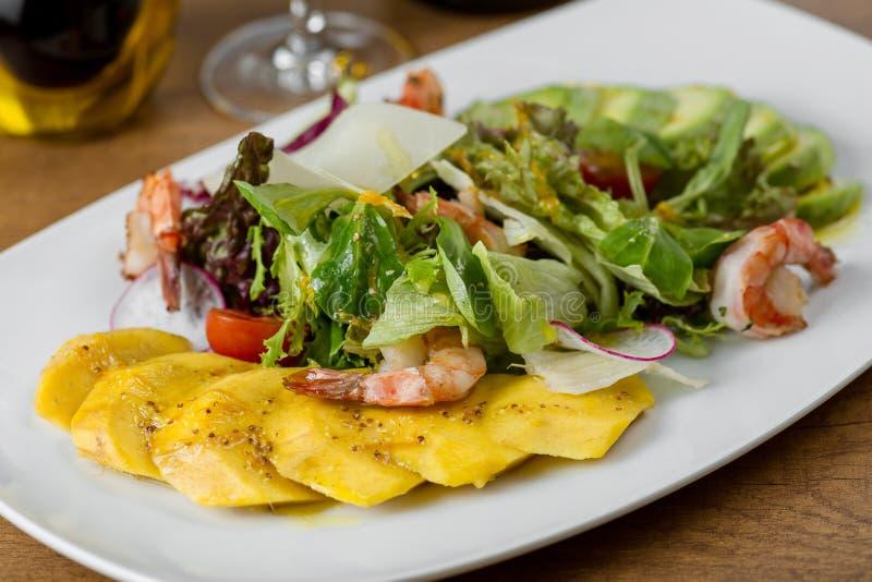 Πιάτο εστιατορίων με τις γαρίδες και μάγκο σε ένα άσπρο πιάτο στοκ φωτογραφία