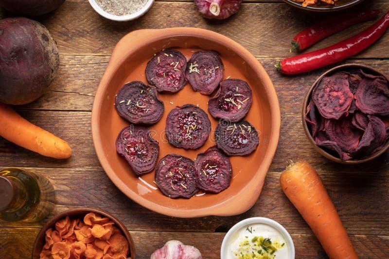 Πιάτο και φλυτζάνια με τα υγιή σπιτικά φυτικά τσιπ και ολόκληρα λαχανικά στο ξύλινο υπόβαθρο στοκ φωτογραφίες