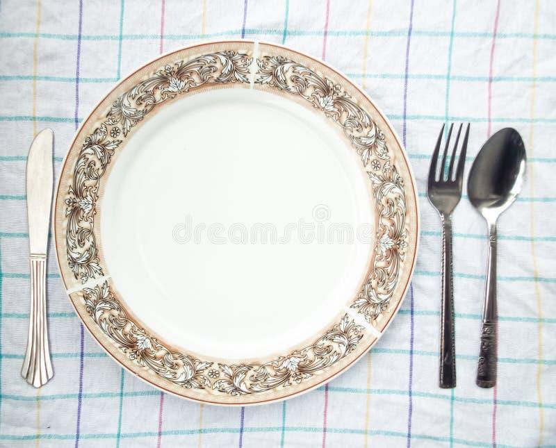 Πιάτο, κουτάλι & δίκρανο στον πίνακα στοκ φωτογραφία με δικαίωμα ελεύθερης χρήσης